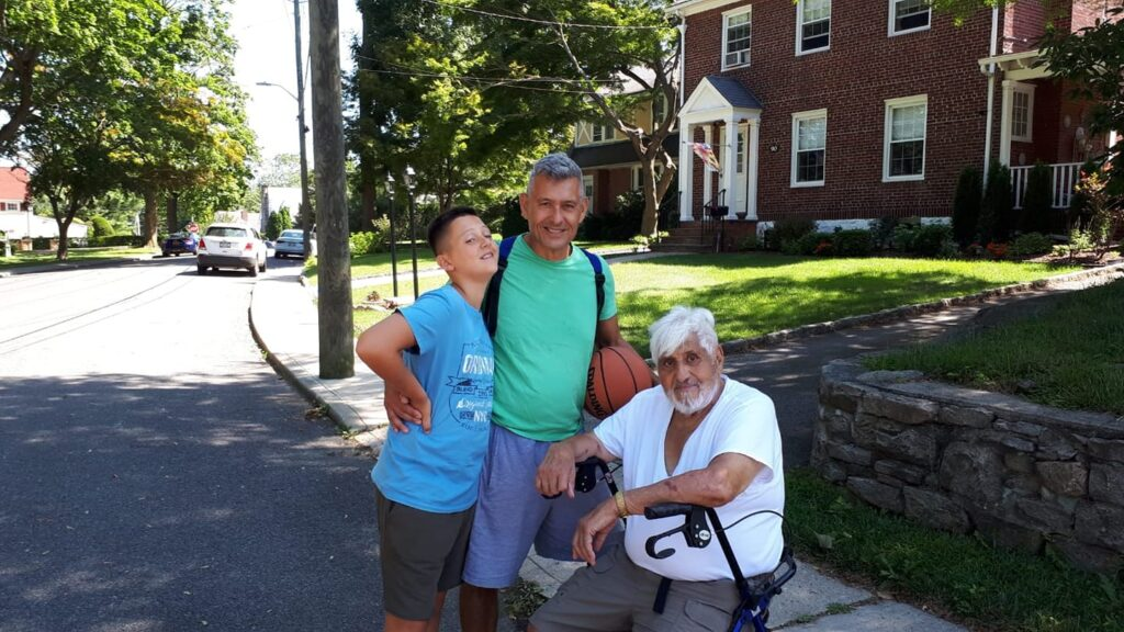 grandson, father and grandfather posing for a picture on a neighborhood street