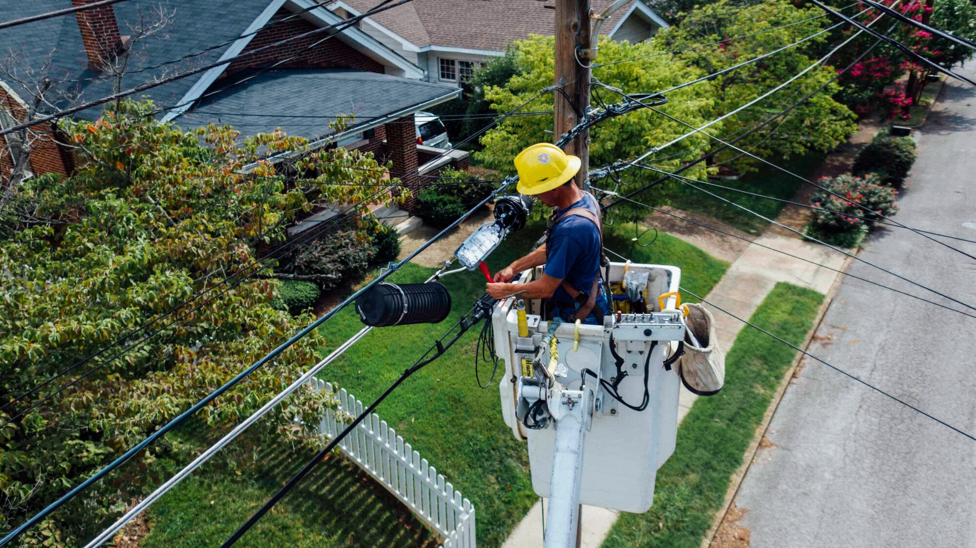 man in a bucket truck with a yellow hard hat working on an electric line